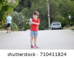 little boy playing with soap... | Shutterstock . vector #710411824