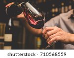 waiter pouring red wine in a... | Shutterstock . vector #710568559