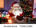 authentic santa claus reading... | Shutterstock . vector #710611384