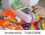Small photo of processes of sewing on the sewing machine sew women's hands sewing machine. sewing machine and female scissors
