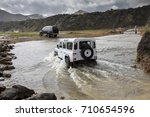 vehicles fording river in landmannalaugar, iceland