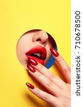 red lips peep through the hole... | Shutterstock . vector #710678500
