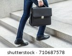 Small photo of Focus on bag. Businessman with briefcase in hand walking up on stairs. Outdoor