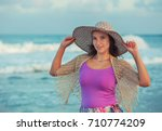 woman with a hat on the beach | Shutterstock . vector #710774209