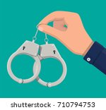 modern metal handcuffs in hand... | Shutterstock .eps vector #710794753