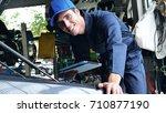 in a garage a mechanic using... | Shutterstock . vector #710877190