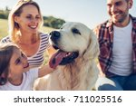 Stock photo beautiful happy family is having fun with golden retriever outdoors mother father and daughter 711025516