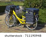 Small photo of LE MANS, FRANCE - AUGUST 31, 2017: Yellow bicycle of a post office La Poste of French city parked on the street of Le mans. postman went to deliver the mail
