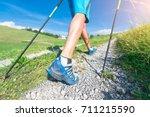 nordic walking on dirt road. | Shutterstock . vector #711215590