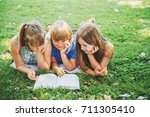 group of three kids lying on... | Shutterstock . vector #711305410