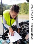 Small photo of Transportation problems - Young woman with car problem on the road