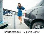 sad woman standing near car... | Shutterstock . vector #711453340