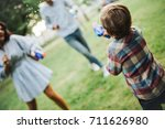baby boy playing water guns... | Shutterstock . vector #711626980