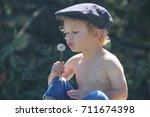 a little boy is blowing a...   Shutterstock . vector #711674398