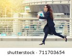 Small photo of Blurred motion of Energetic business woman is running with carrying a briefcase to a business meeting. Competition concept.