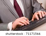 Close-up of businessman hands with pen typing on black computer keyboard - stock photo