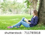 Small photo of Positive student girl adoring reading book