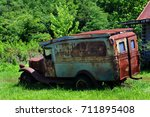 "Small photo of Old jalopy, rusting and broken down, sits besides an abandoned cabin in the Ozarks of Arkansas. You can barely read the sign on the truck that says ""hillbilly."""