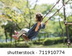 little girl playing with a swing | Shutterstock . vector #711910774