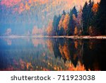 Small photo of autumn landscape in the mountains with trees reflecting in the water at St. Ana's lake, Romania