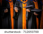 hands holding black hats ... | Shutterstock . vector #712053700