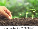 hand planting seed in soil... | Shutterstock . vector #712080748
