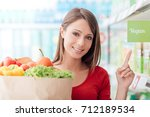 smiling woman shopping at the... | Shutterstock . vector #712189534
