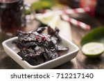 beef jerky on wooden background | Shutterstock . vector #712217140