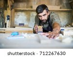 concentrated bearded craftsman... | Shutterstock . vector #712267630