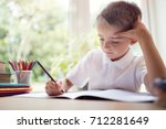 boy writing in a notepad doing... | Shutterstock . vector #712281649