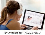 Small photo of Young woman wearing headphones listens online web free audio course at home, student using laptop for e-learning, effective self-education, distance learning program search, rear view over shoulder