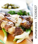 Grilled meat on a skewer as kebab with onion. Close up. - stock photo