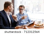 two salesmen discussing plans... | Shutterstock . vector #712312564