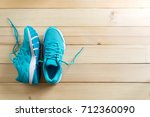 pair of blue sneakers on wooden ... | Shutterstock . vector #712360090