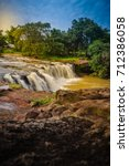 """Small photo of Exotic small waterfall for swimming named """"Tadton Waterfall"""" in Ubon Ratchathani, Thailand. This cascade falls from a rocky bend like a movie screen through the large rock with large water flow."""