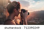 Female photographer, taking pictures of mountain landscape at sunset in Georgia
