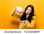 young woman with a piggy bank... | Shutterstock . vector #712420849