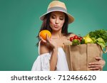 happy woman holding grocery... | Shutterstock . vector #712466620