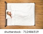 the woman sleeping on the bed.... | Shutterstock . vector #712486519
