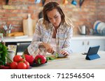 cheerful woman cooking on... | Shutterstock . vector #712546504