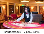 cute lady casino dealer at... | Shutterstock . vector #712636348