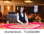 cute lady casino dealer at... | Shutterstock . vector #712636384