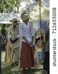Small photo of WHEATON, IL/USA - SEPTEMBER 10, 2017: Two cheerful young women in period dress make a social call at a tent in a military encampment during a reenactment of the American Revolutionary War (1775-1783).
