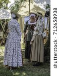 Small photo of WHEATON, ILLINOIS/USA - SEPTEMBER 10, 2017: Three women in period dress enjoy a chat together in a military encampment at a reenactment of the American Revolutionary War (1775-1783).