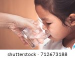 mother hand giving glass of... | Shutterstock . vector #712673188