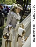 Small photo of WHEATON, IL/USA - SEPTEMBER 10, 2017: A woman in period dress stands looking into a tent by a small girl who contemplates a biscuit at a reenactment of the American Revolutionary War (1775-1783).