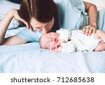 mother kissing her newborn baby.... | Shutterstock . vector #712685638