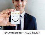 Small photo of Customer Experience Concept, Happy Businessman holding Card with Smiley Face and Five Star Rating for his Satisfaction