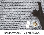 Stock photo black cat sleeping on knitted woolen chunky blanket funny kitty in the warm soft bed scandinavian 712804666