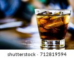 a glass cup of cola on wood... | Shutterstock . vector #712819594